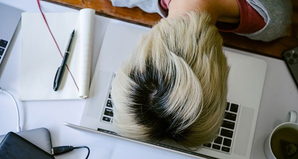 Woman with head on desk in frustration